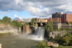 City skyline at High Falls. Rochester, New York. View of High falls waterfall from the Pont De Rennes bridge. Sunshine on the walls of the gorge and city skyline stock photography