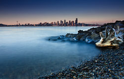 City skyline from a rocky beach. A dreamy look of a city skyline from a beach. The foreground covered with pebbles, rocks and an old tree log. Waves and water Stock Photography