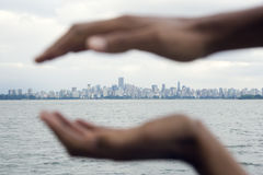 City Skyline Seen Across Water w/ Cupped Hands Royalty Free Stock Images