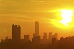 City skyline silhouetted against sunset Stock Photos