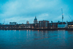City Skyline with St Pauls Cathedral Along Thames. City Skyline with View of Historic St Pauls Cathedral Dome and Construction Cranes Towering Above Low Rise Stock Photo