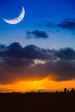City Skyline at Sunrise or Sunset with Moon and Stars. Dramatic blue and orange sky with modern city skyline silhouetted against a stormy. A large moon crecent stock photo