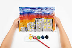 City skyline at sunset, skyscraper with light in window, home silhouette on dark sky background, child drawing, top view hands wit Royalty Free Stock Photos