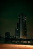 City Skyscraper at Night. Surreal urban scene with buildings, railroad bridge and big empty lot Stock Images