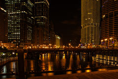 City skyscrapers at night. Golden city skyscrapers illuminated at night, reflecting on river in foreground stock image