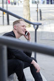 City Smartphone User. Young man sitting on some steps in the city. He is using his smartphone to have a phonecall Royalty Free Stock Images
