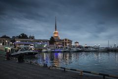 In the city of Sochi, dark nights. An illuminated spire on the shore of the bay with boats pierces the sky covered with leaden clouds Stock Images