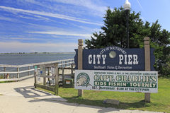 City of Southport City Pier. Southport, NC, USA - September 30, 2015: Southport City Pier and signs entrance to the wooden pier outside on a sunny day. City Pier Stock Image
