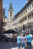 City square with shops, bars and old cathedral clock tower view Stock Photos