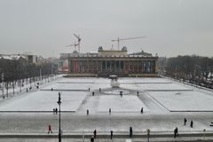 City square in snow. Snow over square in European city with people strolling around and tower cranes in distance, behind building with columns, winter moody day Royalty Free Stock Image