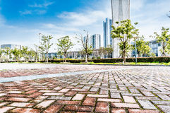 City Square. A texture of City Plaza pavement and the distant background of modern architecture Stock Image