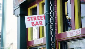 Bar on a City Street. A City Street Bar is a counter or place where beverages, especially liquors, or light meals are served to customers, usually in a festive Stock Image