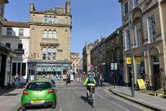 City Street. Bath, UK - May 3, 2016: People and traffic pass along a street in the city centre. Bath is a mid sized city in Somerset granted UNESCO world stock photography