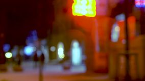 City street in evening. People walking along the city street in evening. Bokeh