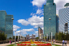 City street with flowers, Astana, Kazakhstan. Astana, Kazakhstan - August 16, 2014. People walk near the main office of the company KazMunaiGaz in Astana. In the Royalty Free Stock Images