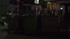 City street with full waste containers, night view. NEA KALLIKRATIA, GREECE - AUGUST 12, 2017: People and cars passing by three full dumpsters in the street stock video footage