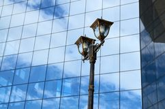 City street lamp against a glass wall. Urban street lamp against a glass wall with a reflection of the sky Stock Photos