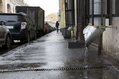 City street, man walking on the sidewalk, the rain, cars parked. Along the road, buildings, puddles, downpipe, spring Stock Image