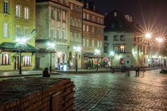 City street at night. Scenic view of old buildings in city street at night with silhouetted people walking on cobbled road Royalty Free Stock Photography
