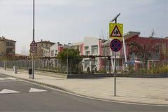 City street with a pedestrian crossing, a speed bump and a caution sign `children` near a beautiful kindergarten. stock photography