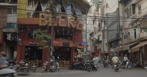 City street with roadside cafe in Hanoi, Vietnam. HANOI, VIETNAM - OCTOBER 27, 2015: View to the street with houses, roadside cafe, parked and driving motorbikes stock video footage