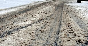 City street under dirty snow. Close up of muddy street surface and tire trucks Stock Photos