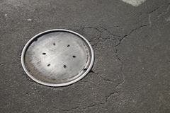 City street walkway with old grunge manhole cover asphalt tarmac royalty free stock photography