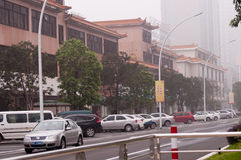City street, Zhongshan China. Zhongshan, China - December 1, 2012: city street with Chinese classical architecture and modern car in fog Royalty Free Stock Photography