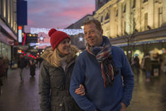 City Stroll On Christmas Eve. Mature couple are enjoying an evening stroll through town at Christmas time royalty free stock image
