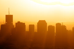 City sunrise. Sunrise over city skyline with rays pouring between buildings
