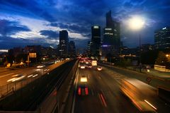 City. Sunset, broken clouds against bright sky, lights of streets. Night falls on city. Sunset, broken clouds against bright sky, lights of streets and big royalty free stock photography