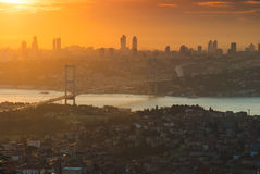 City at sunset with orange sky and bridge Stock Images