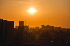 City in sunset time, Silhouettes of houses in the evening haze. And the rays of the setting sun, evening cityscape Royalty Free Stock Photo