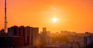 City in sunset time, Silhouettes of houses in the evening haze and the rays of t. He setting sun, evening cityscape Royalty Free Stock Image