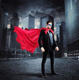 City superhero. Businessman with a superhero cape and mask lands on the asphalt of a city street Stock Images