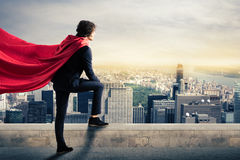 City superhero. Businessman with a superhero cape view from above the city Royalty Free Stock Photos