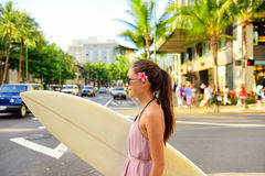 City surf woman surfer with surfboard in Waikiki. Surfer woman walking in city with surfboard to go surfing. Urban Hawaiian surf concept. Asian girl holding surf Royalty Free Stock Photography