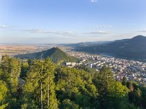 City surrounded by forest. The forest and the city in the valley at sunset. Aerial view in Romania, Piatra Neamt Stock Image