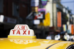 City Taxi with Chinese sign. A taxi sign with the Chinese characters 'ren ge'.  Ren ge means the taxi driver doesn't belong to a company.  It's a city scene but Royalty Free Stock Photo