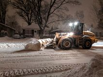 Service snow plowing truck cleaning residential street during heavy snowstorm, Toronto, Ontario, Canada. stock image