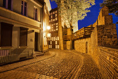 City of Torun at Night. Poland, Torun, Leaning Tower and and cobbled street at night along city wall in the Old Town stock photography