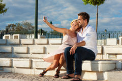 City tourism - couple in vacation on a bench Stock Images