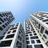 City towers under blue sky. 3d render. Abstract modern architecture. Perspective of tall city towers under blue sky. 3d render illustration Stock Photos