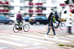 City traffic. With bicycle riders, pedestrian and cars in motion blur Royalty Free Stock Photography