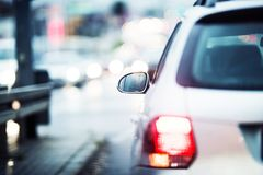 City Traffic Drive. Car Outside Mirror in Focus. City Commute Concept Royalty Free Stock Photography