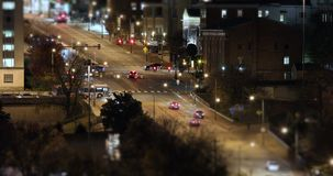 City Traffic Intersection Night Time Lapse in Shallow Depth of Field. Traffic going down a city hill and through an intersection at night in time lapse with stock footage