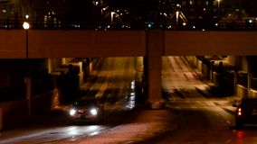 City traffic at night. Traffic going under an underpass in the city at night stock video footage