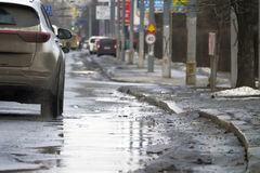 City traffic during spring thaw. Road with puddles. City traffic during spring thaw. Dirty road with puddles Royalty Free Stock Photography