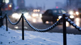 City traffic on a winter evening. Defocused cars with bright headlights passing by slowly, chain road border in the foreground stock footage