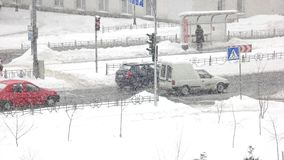 City traffic in winter time. Traffic on the street during a snow storm in winter. Winter city life stock footage
